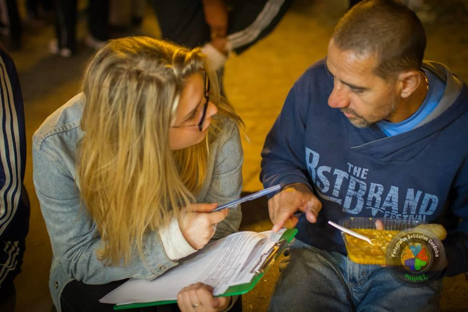 A student assists a homeless man during her Human Rights internships in Argentina.
